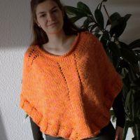 En lyserød/orange poncho – lynstrikket på rundpinde
